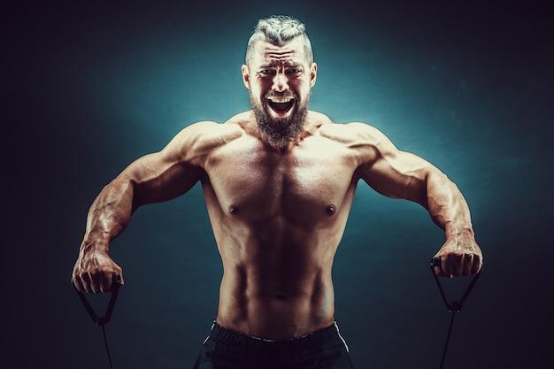 バンドを伸ばして運動フィットネス男。弾性ゴムバンドで運動する筋肉のスポーツ男。ゴムバンドでワークアウトする男。フィット感、フィットネス、運動、トレーニング、健康的なライフスタイル