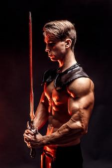 Портрет сексуальный мускулистый концентрированный мужчина держит меч.