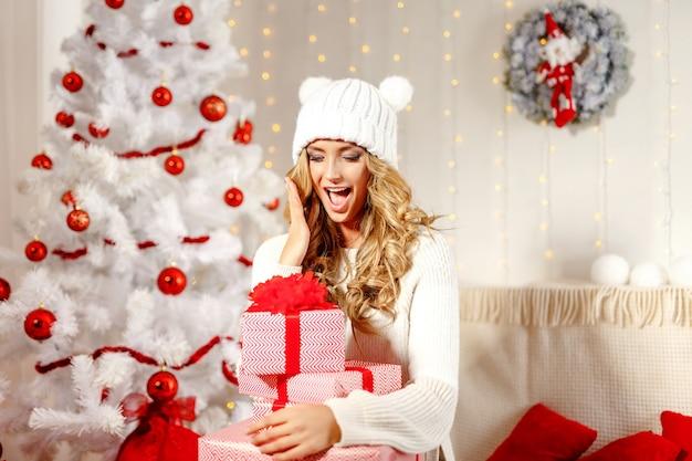 Очаровательная женщина позирует с рождественскими подарками