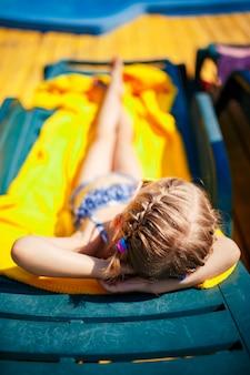 小さな女の子はリゾートのプールの近くのサンベッドで日光浴をしています