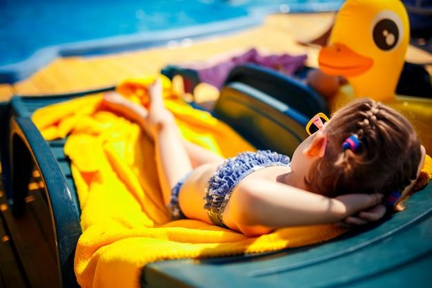 Маленькая девочка загорает на шезлонге возле бассейна на курорте