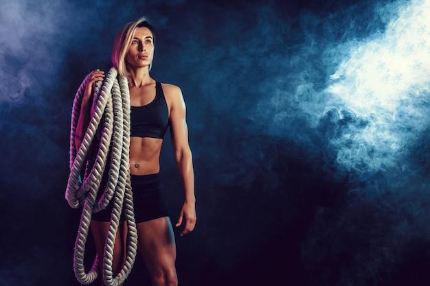 暗い壁に彼女の肩に重いロープで黒のスポーツウェアで魅力的な女性。強さと動機。重いロープを扱うスポーティな女性。