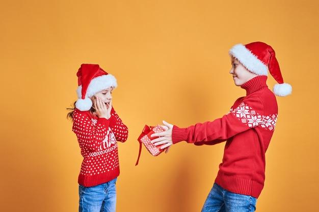 驚いた少女にクリスマスプレゼントを渡す少年