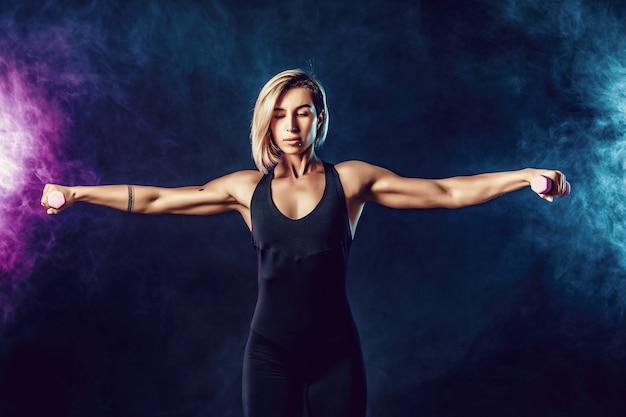 ファッショナブルなスポーツウェアで魅力的なスポーティなブロンドの女性は、ダンベルでエクササイズを行います。煙で暗い壁に筋肉の女性の写真。強さと動機。
