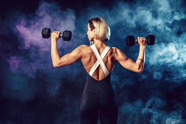Вид сзади спортивная женщина в модной спортивной одежды делает упражнения с гантелями. фото мышечной женщины на темной стене с дымом. сила и мотивация.