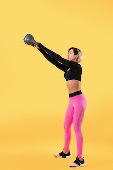 ファッショナブルなピンクと黒のスポーツウェアのフィットネス女性は、黄色の壁にケトルベルでエクササイズします。強さと動機。