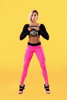 黄色の壁にケトルベルを保持しているファッショナブルなピンクと黒のスポーツウェアのフィットネス女性。強さと動機。