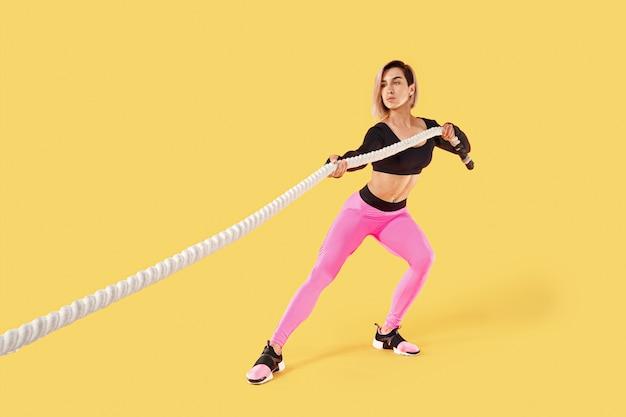 強い女性がロープを引っ張る。黄色の壁に分離されたピンクと黒のスポーツウェアでスポーティな魅力的な女性の写真。強さと動機。