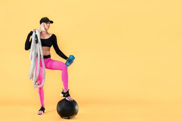 重いロープ、黄色の壁にシェーカーとピンクと黒のスポーツウェアの魅力的な女性。強さと動機。重いロープを扱うスポーティな女性。