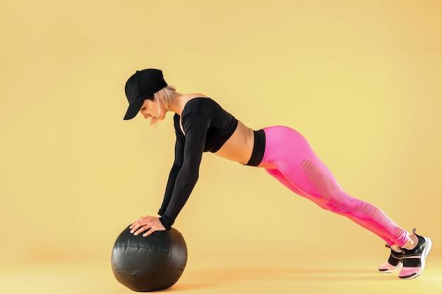 Женщина в фитнес одежда тренировки с мячом медицины. спортсменка делает живот тренировки с помощью медицины мяч.