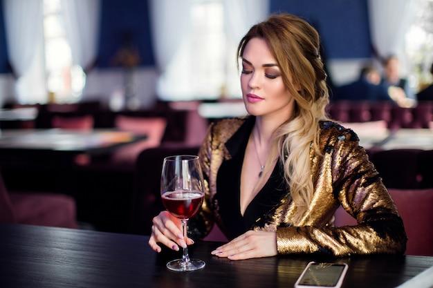 つるを飲んでカフェでエレガントな服で巻き毛の美しい官能的な女性のファッション写真
