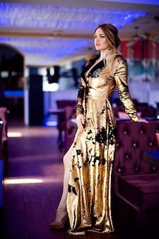カフェでエレガントな服を着た巻き毛の美しい官能的な女性のファッション写真