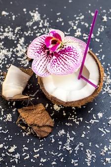 Кокосы с кокосовой стружкой и орхидеей на сером фоне камня