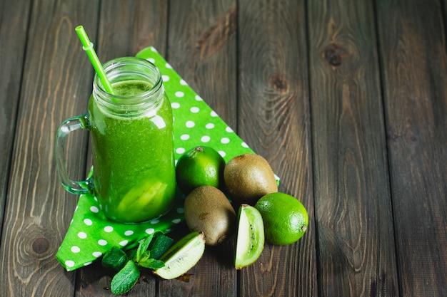 木製のテーブルに食材をブレンドした緑のスムージー