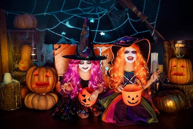Две милые смешные сестры празднуют праздник. веселые дети в карнавальных костюмах готовятся к хэллоуину.