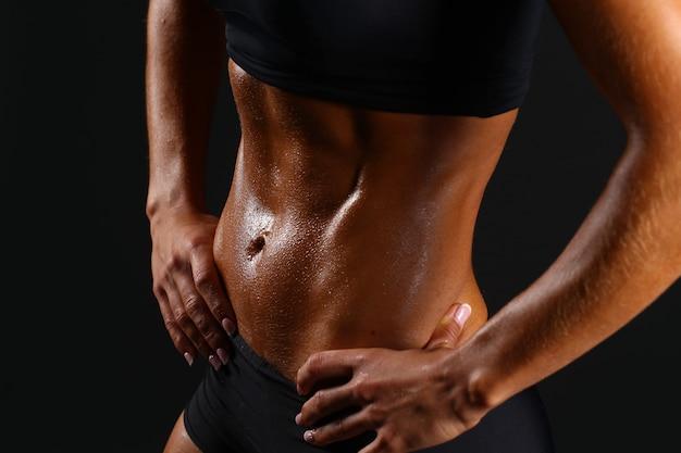 Спортивная сексуальная девушка с большими мышцами живота в черной спортивной одежде.