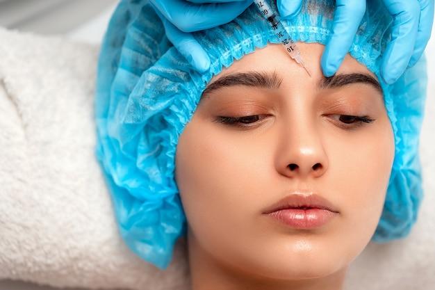 美容師は、美容院で女性の顔の皮膚のしわを引き締め、滑らかにするために、若返りの顔の注入手順を行います。美容スキンケア