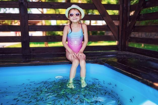 小魚とマッサージを受ける若い女の子。