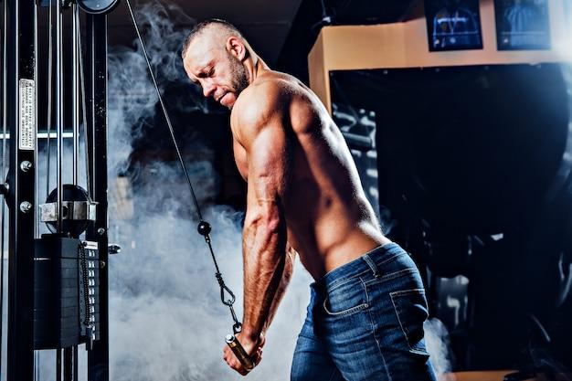 エクササイズを行うジムでワークアウトする筋肉の男