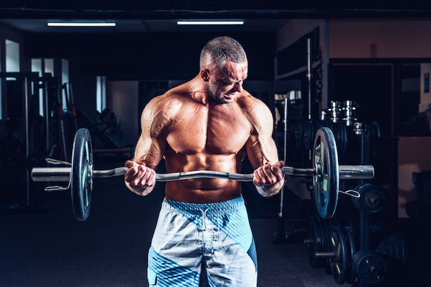 ジムで大きなダンベルで上腕二頭筋の演習を行う筋肉ボディービルダー男