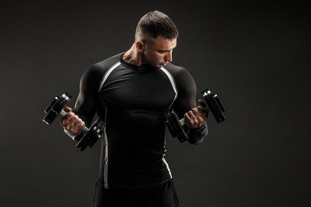 ダンベル運動を行う筋肉の男を集中