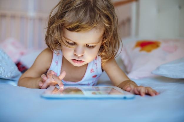 小さな女の子がタブレットを再生