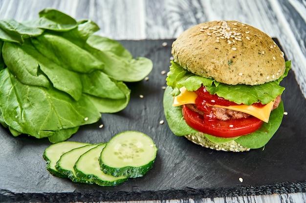 緑色のパンと新鮮な野菜のハンバーガー