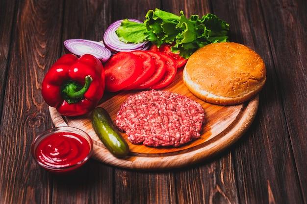 生のひき肉、ハンバーガーステーキカツレツ、調味料、チーズ、トマト、サラダ、ヴィンテージの木製ボード上のパン