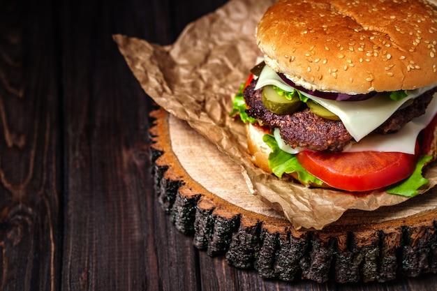 Крупный план самодельных бургеров говядины с салатом и майонезом служил на маленькой деревянной разделочной доске.