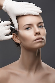 化粧品の注入を得る若い女性の肖像画