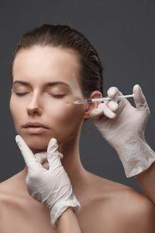 Портрет молодой женщины получают косметические инъекции