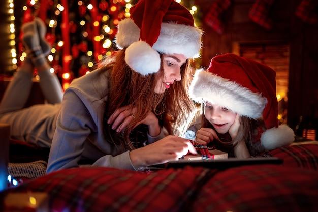 サンタの帽子とパジャマで面白いビデオを見ている母と娘の笑顔