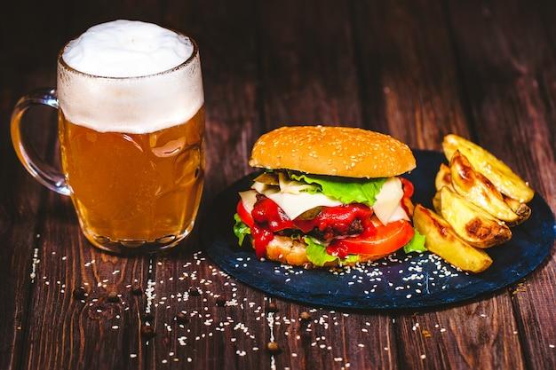 Аппетитный домашний аппетитный бургер из говядины с салатом и картофелем, бокал пива на каменной разделочной доске. темно