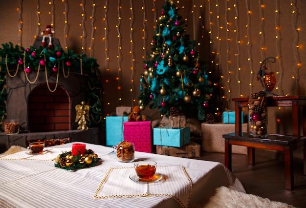 ライトで飾られたクリスマスツリーのあるリビングルームには、プレゼント、屋内のガーランド照明があります
