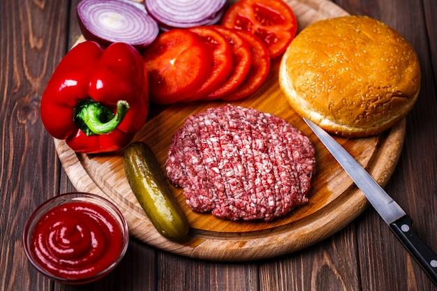 生のひき肉、ハンバーガーステーキ、カツレツ、調味料、チーズ、トマト、サラダ、パンにヴィンテージの木製ボード