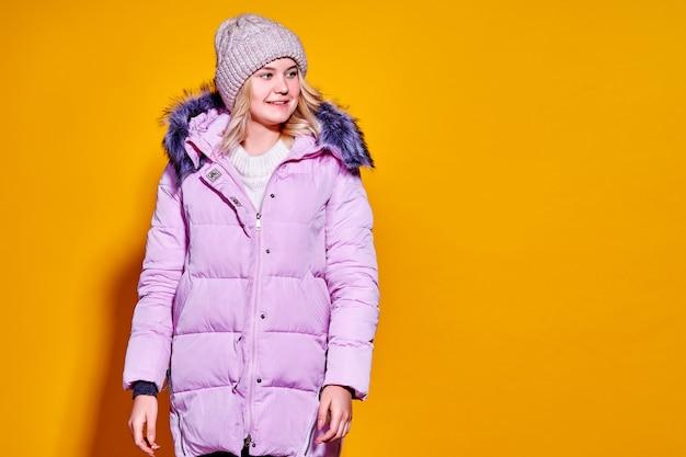 Молодая модная женщина в коротком фиолетовом пуховике