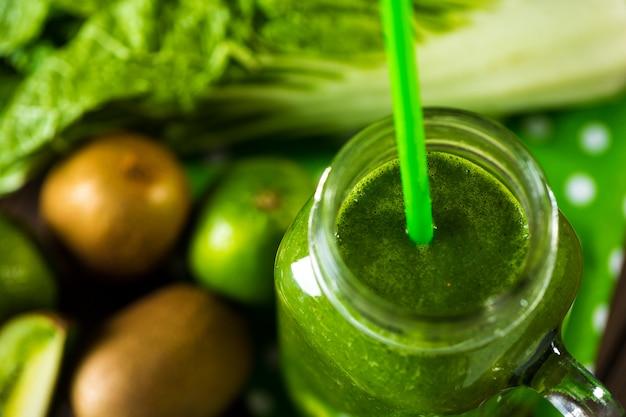 Смешанный зеленый коктейль с ингредиентами на деревянный стол