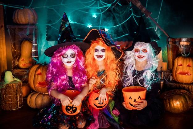 Три милые смешные сестры празднуют праздник. веселые дети в карнавальных костюмах готовятся к хэллоуину.