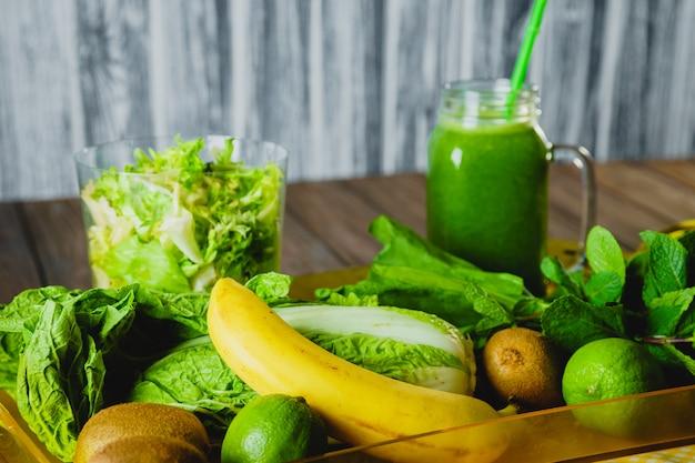木製のテーブルの選択と集中に食材をブレンドした緑のスムージー。