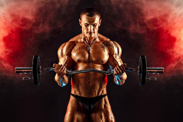 赤い煙でダンベルを持ち上げる筋肉の男の肖像