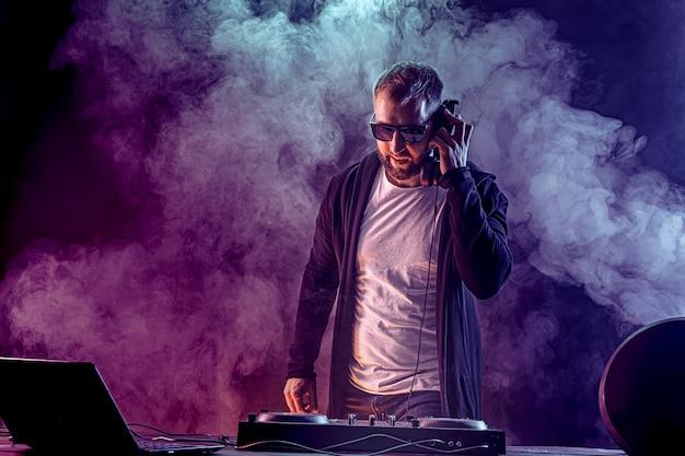 Молодой стильный человек в очках позирует за микшерный пульт на цветной дымовой студии