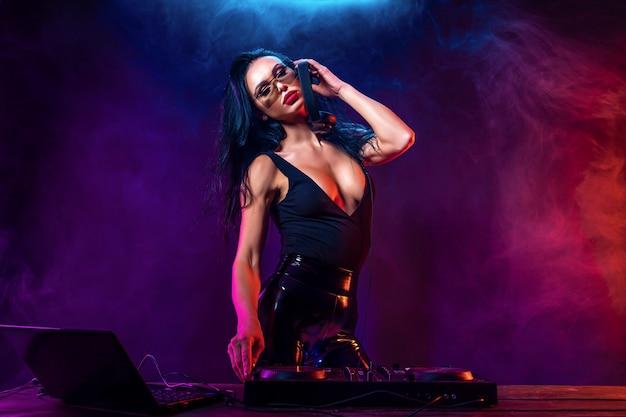 Молодой сексуальный диджей в темных очках играет музыку