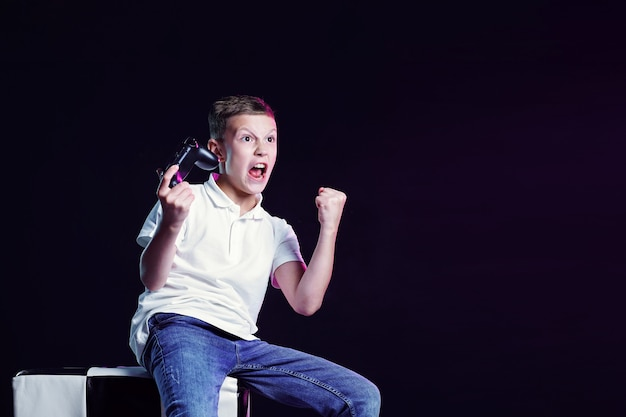Счастливый мальчик с открытым ртом и криком радости после победы в видеоигре на черной стене