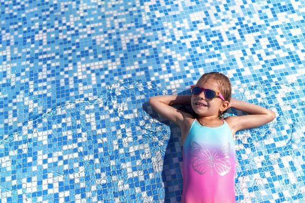 Маленькая девочка в солнцезащитные очки и шляпа с единорогом в открытом бассейне роскошного курорта на летние каникулы на тропическом пляже острова