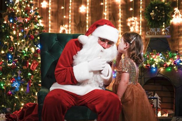 Маленькая девочка шепчет на ухо санта-клауса. рассказать секрет. раскрытие подарка, который вы хотели бы выиграть