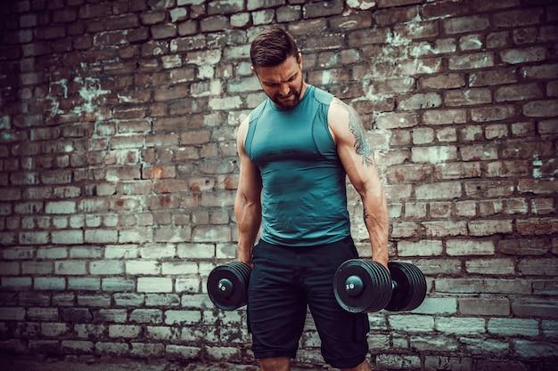 レンガの壁にダンベルで運動をしている筋肉男