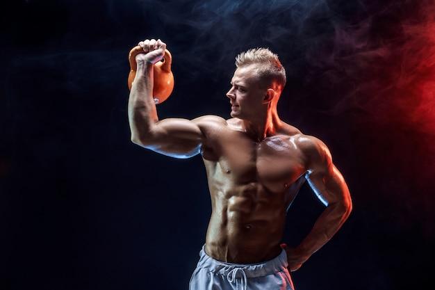 Концентрированный мускулистый мужчина делает упражнения с гирей