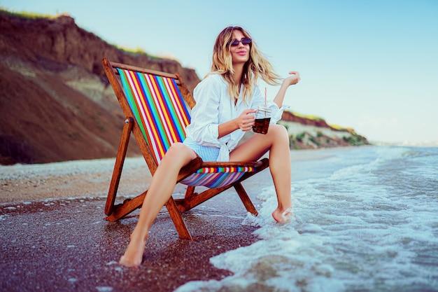 Довольно блондинка в форме сердца солнцезащитные очки, белая рубашка и раздетый купальник отдыхают на шезлонге на пляже и пьют коктейль. концепция летних каникул