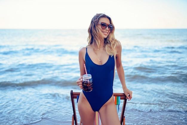 Потрясающая красота белокурая женщина в солнцезащитные очки, купальник отдыха на пляже и напитки коктейль. концепция летних каникул