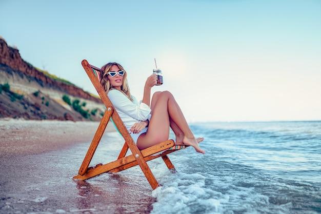 Красивая женщина, отдыхая на пляже лежак и пьет газированную воду. концепция летних каникул